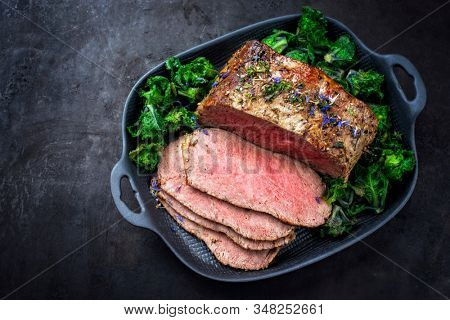 Traditional Commonwealth Sunday roast with sliced cold cuts roast beef with kalette and herbs as top view on a modern design pan with copy space left  stock photo
