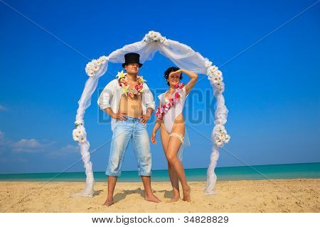 Groom with bride wearing lei, standing under archway on beach, peering into the distance stock photo