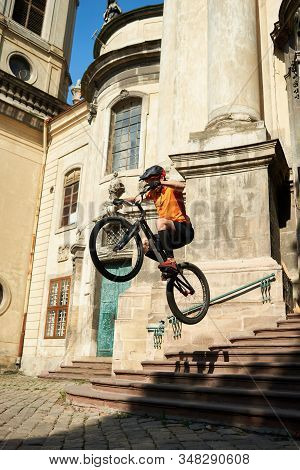 View from below man in orange sportswear jumping from steps on a bicycle. Athlete in downtown on architecture background doing new tricks on sports bike. Concept of sports accessories. stock photo