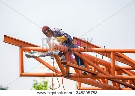 The welding workers at structures site. Worker is welding steel structures. Workers are also working at high altitude with a set of fall protection devices. stock photo