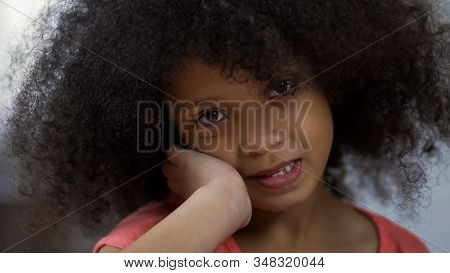 Adorable african girl smiling at camera, positive emotions, childhood concept stock photo