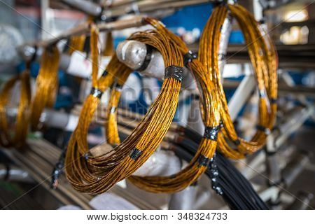 Twisted copper wire hangs on metal racks in the production of large industrial parts and for machine and shipbuilding. Spare parts concept and parts for electronic equipment stock photo