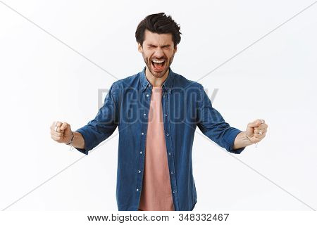 Successful good-looking male finally got signed huge deal, clench arms fist pump and yelling from happiness and joy, feeling lucky close eyes as triumphing, excited receive award, white background stock photo