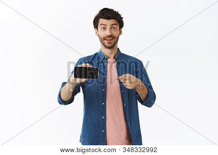 Technology, advertisement and people concept. Attractive surprised excited man with beard, telling about interesting app or news heart online, pointing at smartphone screen, holding mobile horizontal stock photo