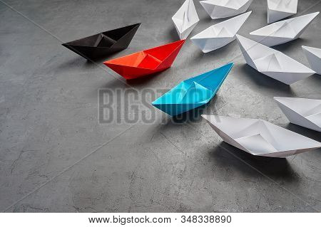 Business Concept, Paper Boat, the key opinion Leader, the concept of influence.Red,blue and black paper boat as the Leader, leading in the direction of the white ships on a gray concrete background,copy space stock photo