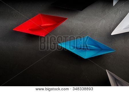 Business Concept, Paper Boat, the key opinion Leader, the concept of influence.Red.blue and black paper boat as the Leader, leading in the direction of the white ships on a gray concrete background,flat lay. stock photo