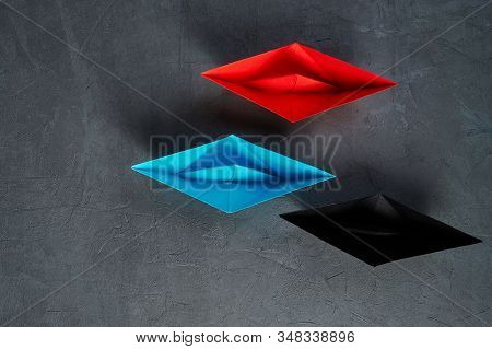 Business Concept, Paper Boat, the key opinion Leader, the concept of influence.Red.blue and black paper boat as the Leader on a gray concrete background,copy space stock photo