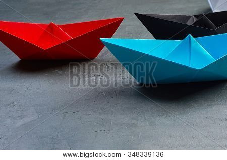 Business Concept, Paper Boat, the key opinion Leader, the concept of influence.Red.blue and black paper boat as the Leader on a gray concrete background stock photo