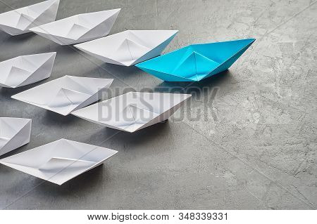 Business Concept, Paper Boat, the key opinion Leader, the concept of influence. One blue paper boat as the Leader, leading in the direction of the white ships on a gray concrete background,copy space stock photo
