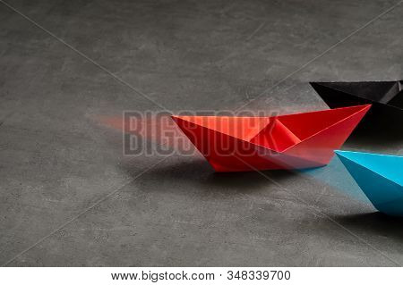 Business Concept, Paper Boat, key opinion Leader, the concept of influence.Red.blue and black paper boat as the Leader on a gray concrete background,copy space stock photo
