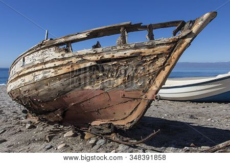 old abandoned wooden boat on the beach, an old shipwreck boat abandoned stand on beach or Shipwrecked off the coast of Cabo de Gata, Almeria, Andalusia, Spain, old rusty wooden boat stock photo