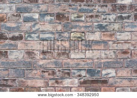 A weathered worn red stone wall in closeup stock photo