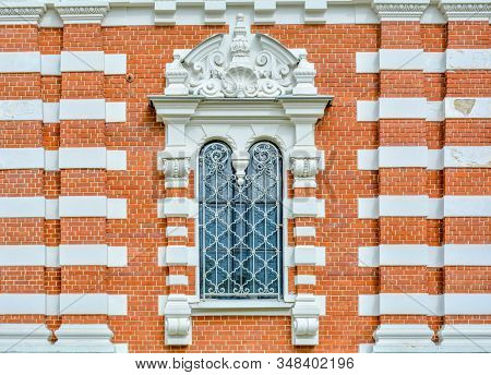 Close-up of ancient vintage arch window with cast iron white painted deorative lattice and white antique plaster patterns stock photo