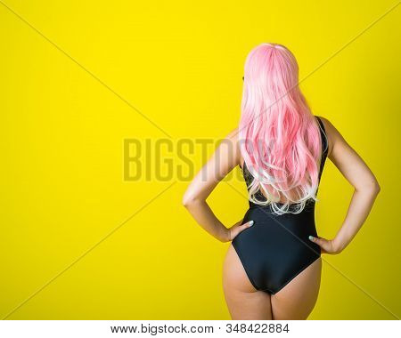 A woman with long wavy artificial hair is standing back in a black swimsuit. Fashion girl in a curly pink wig on a yellow background. stock photo