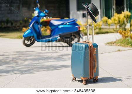 Blue new SUITCASE with a black hat, stands on the street, against a background of tropical Palm trees, a scooter and a hotel complex. The concept of vacation and travel in Thailand. stock photo