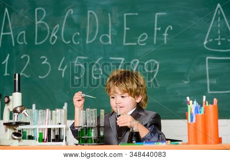 Basic knowledge primary school education. Educational experiment. Boy microscope and test tubes school classroom. Knowledge concept. Fascinating subject. Knowledge day. Kid study biology chemistry stock photo