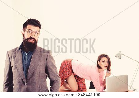 Boss feeling shock. Shocked boss and his sexy tempting subordinate on desktop. Caucasian boss and sexi coworker in office. Bearded boss with pretty employee working in background stock photo