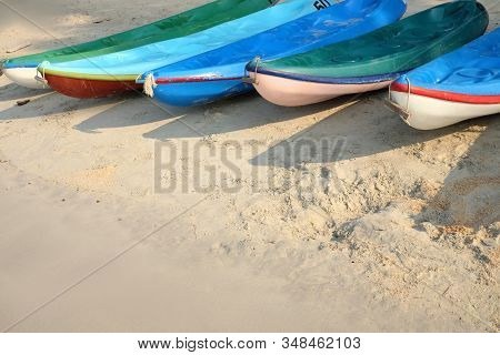 Kayaks near the water on sand beach. Colorful boats in front of sea coast. Vacation and travel sport activity. Free copy space. stock photo