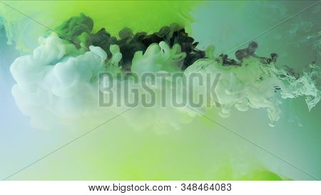 Multicolored composition from ink streams. Black and white streams of ink float and mix in the center of the composition. Colorful abstract combination of acrylic rainbow ink on a light green background. Ink in water, slow motion. stock photo
