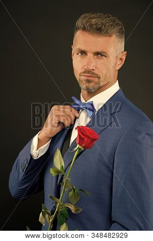 Valentines day and anniversary. Dating services. How to be romantic. Perfectionist concept. Romantic gentleman. Man mature confident macho with romantic gift. Handsome guy rose flower romantic date. stock photo
