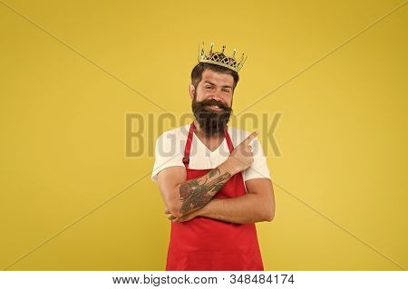 Royal recipe. Man king cook wear cooking apron and golden crown. Kingdom of tastes. Chief cook and professional culinary. Premium quality. Cook food. Cook with beard and mustache yellow background. stock photo