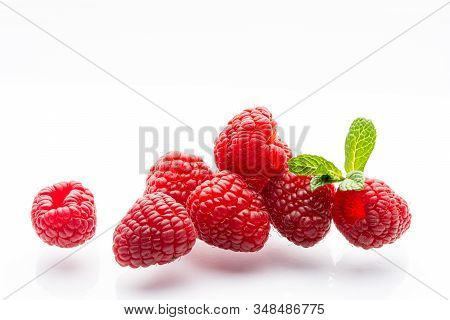 Ripe raspberries on a white background. A sprig of fresh mint. Berries. Garden raspberries. White background. Red berries. Isolated. stock photo
