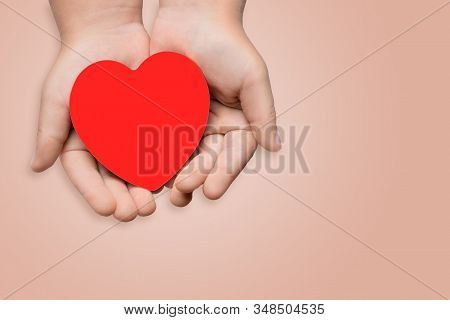 Childrens hands hold a red heart. Health concept, donate, world heart day. stock photo