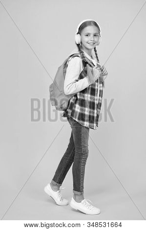 Student. Modern education. Energetic cheerful teen listening music. Stylish schoolgirl going to school. Girl little fashionable girl with backpack. School life. Happy carefree child. School classes. stock photo