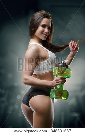 Fitness woman drinking water at workout in the gym. Pretty caucasian girl exercising cross fitness and bodybuilding sport concept. Trains Abs muscle butt  and booty exercises in gym naked torso stock photo