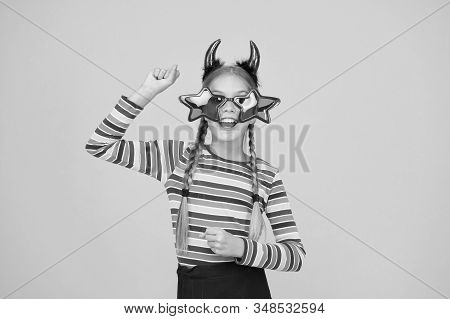 Getting ready for costume party. Party girl on yellow background. Small child wear halloween party accessories. Halloween kid with party look. Holiday celebration. Happy holidays. stock photo