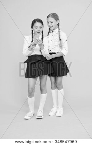 Girls school uniform using smartphone. Schoolgirls use mobile phone or smartphone to share photos. School application smartphone. Internet is wonderful resource but access to it has hazards for kids. stock photo
