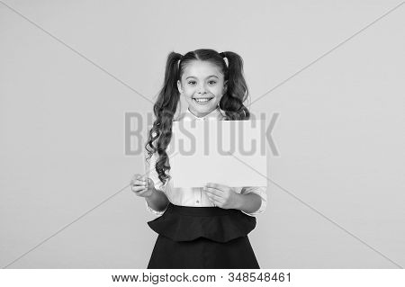 Get a writing pen. Little girl holding blank paper sheet for writing task on yellow background. Small child display green poster for writing information. Empty show card for writing, copy space. stock photo