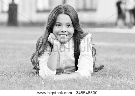 Mental wellness. Little schoolgirl. Relax at school yard. Kid relaxing outdoors. School break for rest. Adorable pupil. Girl kid laying lawn. Girl school uniform enjoy relax. Importance of relaxation. stock photo