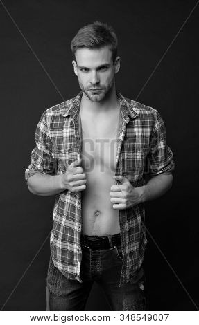 Full of desire. Perfect body. Muscular chest. Masculine traits concept. Male fashion and beauty. Sexy muscular macho. Athlete man undressing. Muscular guy. Man confident face taking off shirt. stock photo