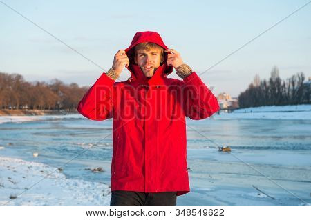 Exploration of polar regions. Winter destinations. Winter fishing. Safety measures. Polar explorer. Winter menswear. Winter outfit. Comfortable outfit. Man warm jacket snowy nature background. stock photo
