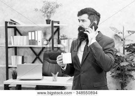 Man bearded businessman hold cup and smartphone. Coffee is pledge of successful negotiations. Caffeine addicted. Mobile call. Start day with coffee. Coffee relaxing break. Boss enjoying energy drink. stock photo