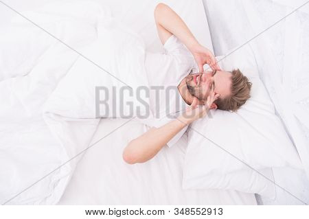 Migraine headaches. Handsome man relaxing in bed. Snoring can increase risk headaches. Common symptom of sleep apnea. Causes of early morning headache. Sleep problems can lead to headaches in morning. stock photo