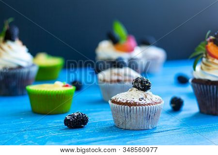 Freshly baked sweet muffins on a blue background. Sweet pastries, recipes, cooking stock photo