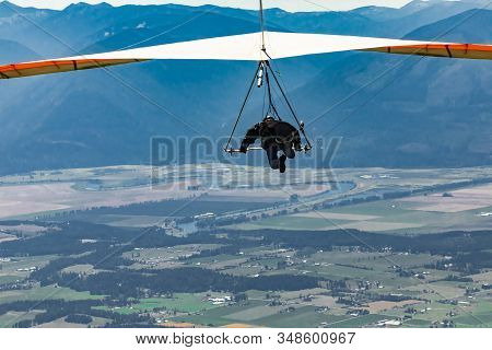 Flying hang glider in action. Extreme air sports. Recreational leisure in Creston, British Columbia, Canada. Man hang gliding stock photo