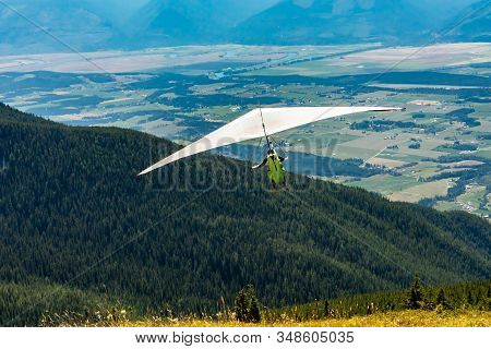 Hang gliding in action. Extremal air sports. Recreational leisure activities. Scenic view over Kootenay valley mountains, Canada stock photo