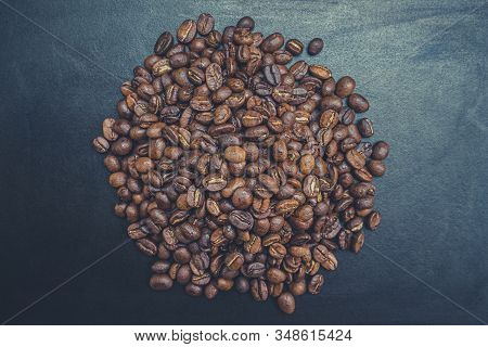 Above view of dark roasted coffee beans pile on dark background. Seed nature from top view. Group agriculture grain arabica. stock photo