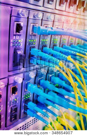 Fiber Optic cables connected to optic ports and UTP, Network cables connected to ethernet ports stock photo