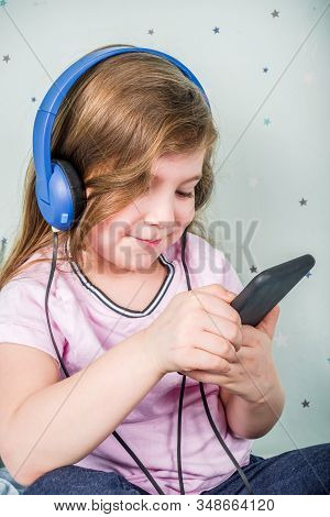 Kids Gaming video games concept. Toddler or young girl, playing game with joystick, smart-phone, VR glasses and headphones, enjoying games, sitting on sofa in living room at home. stock photo