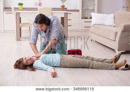Young couple in first aid concept at home stock photo