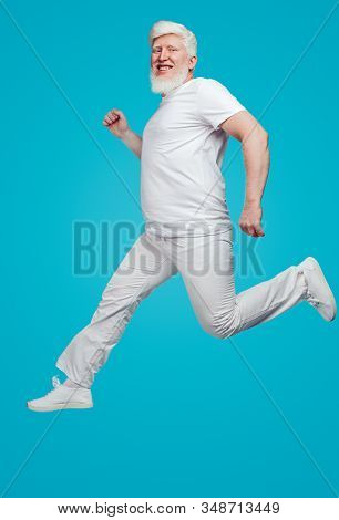 Side view of happy active adult bearded albino male in white outfit running and looking at camera on blue background stock photo