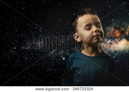 a small child imagines himself to be an astronaut in an astronaut's helmet. Elements of this image furnished by NASA stock photo