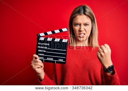 Young beautiful woman holding clapboard standing over isolated red background annoyed and frustrated shouting with anger, crazy and yelling with raised hand, anger concept stock photo