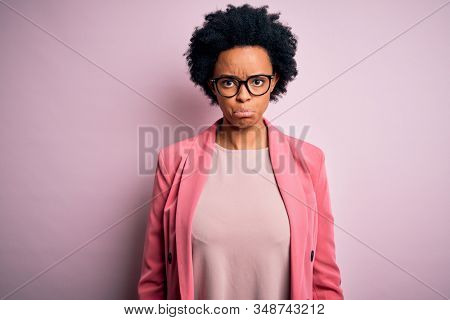 Young beautiful African American afro businesswoman with curly hair wearing pink jacket depressed and worry for distress, crying angry and afraid. Sad expression. stock photo