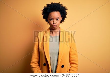 Young beautiful African American afro businesswoman with curly hair wearing yellow jacket depressed and worry for distress, crying angry and afraid. Sad expression. stock photo