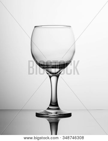 Empty wine glass black and white. Photo of a single empty round glass wine glass. stock photo